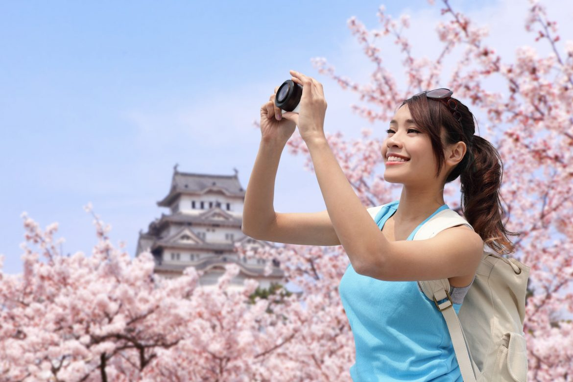 27093526 - happy woman traveler take photos by camera with cherry blossoms tree and castle on vacation while spring